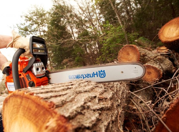 man using a Husqvarna 440E to cut wood