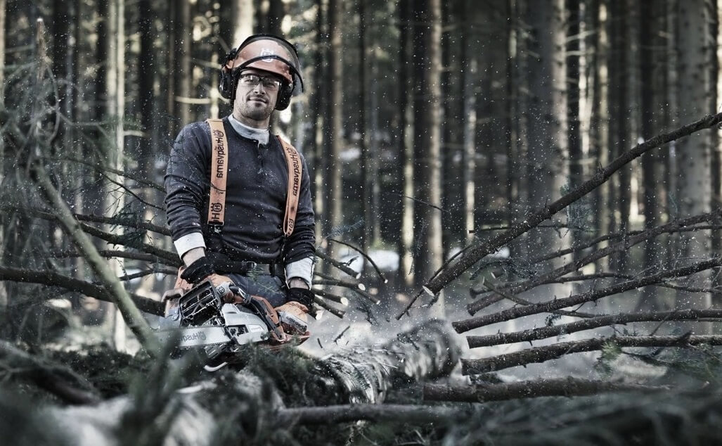 man using a Husqvarna chainsaw in the woods