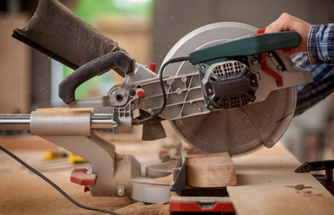 man working with miter saw in the workshop